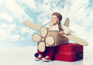 Little Child Playing Airplane Pilot Kid Traveler Flying in Aviator Helmet on Travel Suitcase Vacation Trip Concept over Blue Sky Clouds